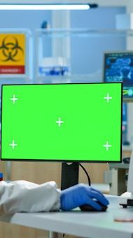 보호복을 입은 과학자 남자는 현대적인 시설을 갖춘 실험실에서 녹색 흉내를 내며 컴퓨터에 타이핑을 하고 있습니다. 크로마 키, 격리된 디스플레이가 있는 장치에서 백신 연구를 하는 미생물학자 팀.