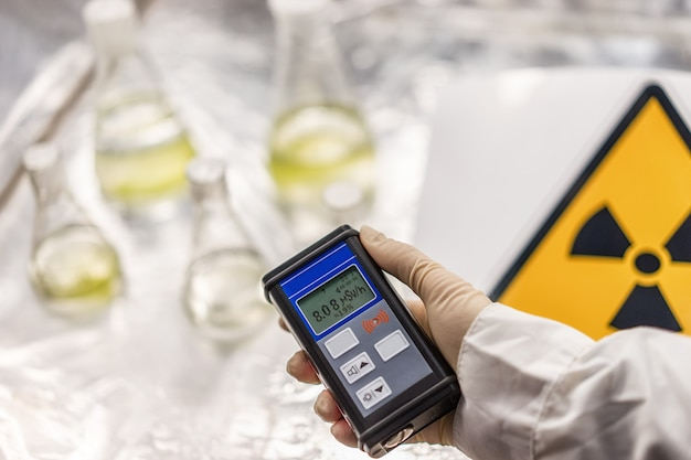 The scientist measures the level of radiation on the sign of radiation hazard with the help of a dosimeter