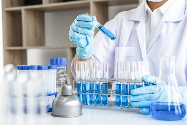 Scientist or medical in lab coat holding dropper with reagent, mixing reagents in glass flask