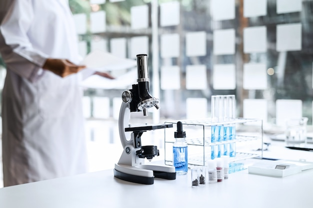 Scientist or medical in lab coat holding test tube with microscope
