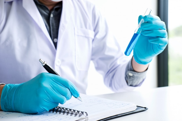 Scientist or medical in lab coat holding test tube with reagent with drop of color liquid over glass equipment working