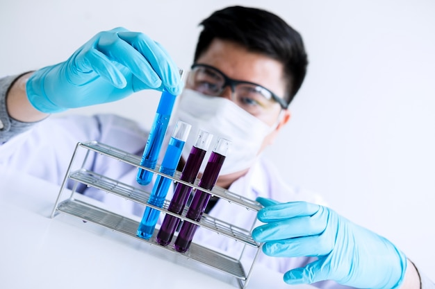 Scientist or medical in lab coat holding test tube with reagent with drop of color liquid over glass equipment
