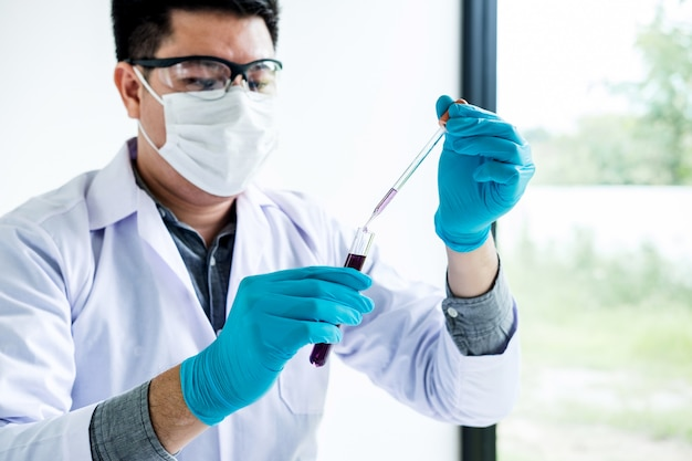 Scientist or medical in lab coat holding test tube with reagent with drop of color liquid