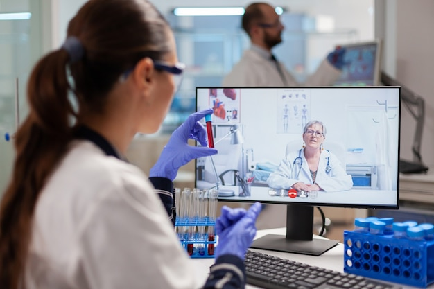 Scientist in medicine laboratory discussing with professor during video online conference showing blood test tube. chemist examining vaccine evolution using high tech researching treatment.