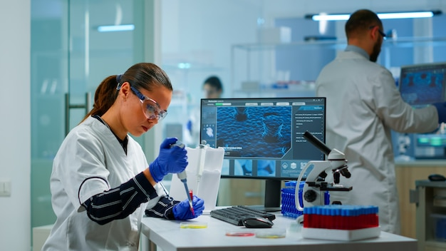 Scientist in modern equipped medical laboratory examinining drug discovery with micropipette. medical stuff examining vaccine evolution using high tech and technology researching treatment, developmen