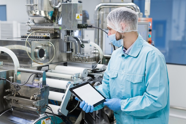 Scientist near steel machine hold empty tablet