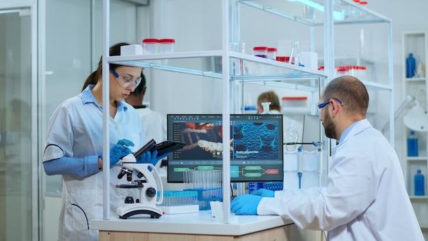 近代的な設備の整った実験室でタブレットにメモを取っている科学者の看護師。 covid19ウイルスに対する治療法開発の研究のためにハイテクを使用してワクチンの進化を調べる多民族チーム