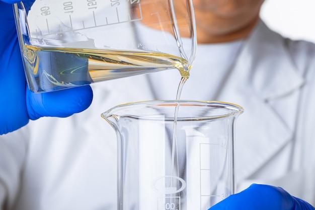 플라스 크에 일부 노란색 액체를 붓는 파란 장갑에 과학자 또는 의사