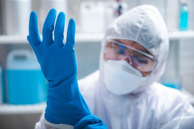医学研究所で働くための手袋とマスクを身に着けている科学者または医師、ウイルス病の流行性インフルエンザ、診療所または病院での健康安全衛生のための保護ユニフォーム
