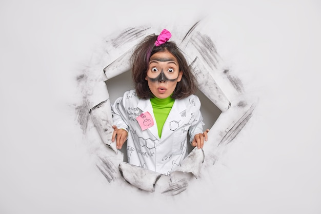 Ученый-фармаколог разрабатывает новый вид лекарств или косметических средств, ошеломленный, чтобы получить неожиданные результаты экспериментов, носит унифицированные позы через бумажную дырочку, проводит научные исследования