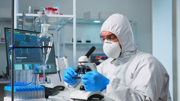 Scientist in ppe suit placing a slide on specimen stage of a laboratory microscope making adjustments. chemist in coverall working with various bacteria, tissue blood samples for antibiotics research