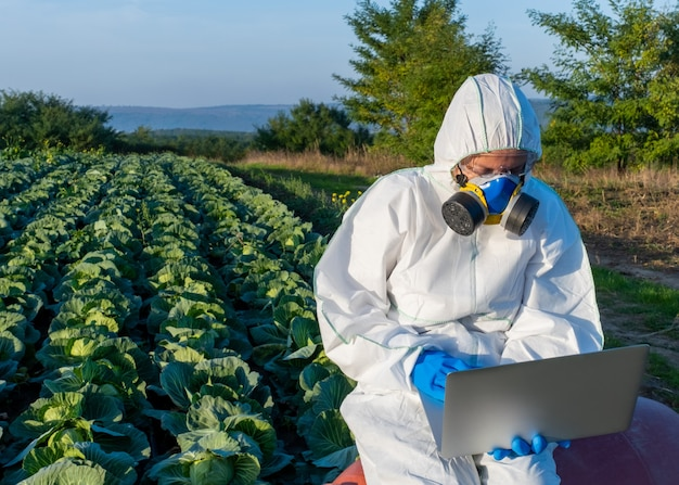 Scientist  protective equipment chemical mask glasses uses laptop  farm field