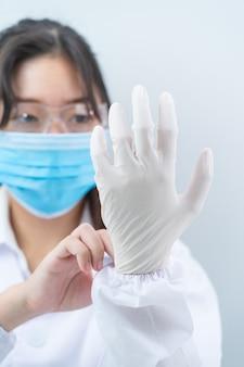 Ученый надевает нитриловые перчатки