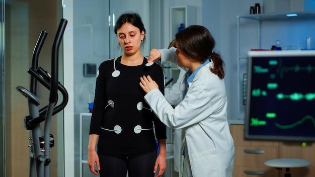科学者の研究者は、専門の身体機器に電極を取り付ける耐久試験のために女性患者を準備しています。パティネット、vo2、ekgスキャンの健康状態を監視する医師のチームがコンピューター画面で実行されます