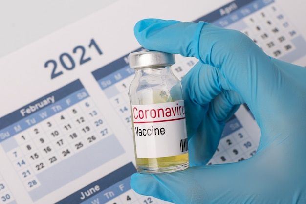 Scientist researcher with coronavirus vaccine in front of calendar of 2021 year. concept of discovering vaccine in 2021