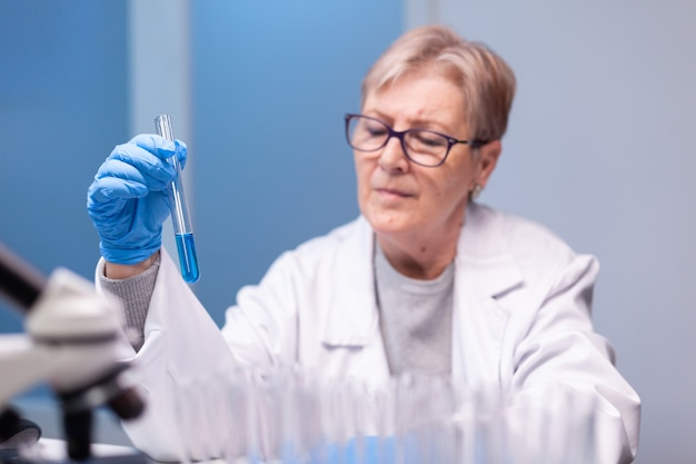 Scientist senior woman looking into test tube for biochemistry test