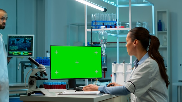 Scientist sitting at desk working on personal computer with mock-up green screen. in background man lab researcher discussing with doctor about vaccine developent bringing blood samples