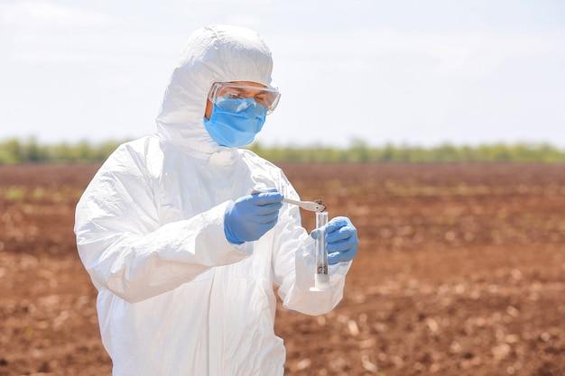 Ученый, изучающий образцы почвы в поле