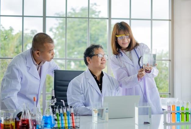 Ученый команда и старший улыбается рабочий ноутбук