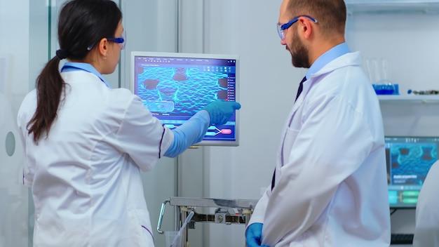 과학자 팀은 현대적인 장비를 갖춘 실험실에서 바이러스 개발을 보고 있는 컴퓨터 앞에서 논쟁합니다. 치료 연구를 위해 첨단 기술을 사용하여 백신 진화를 분석하는 다민족 물건.