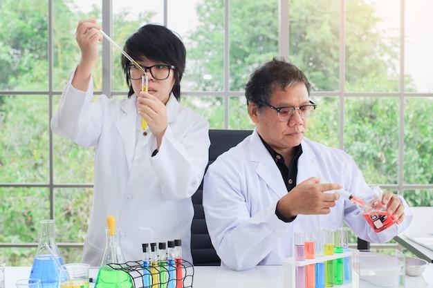 Ученые команды, изучая с цветовой пробиркой в лаборатории