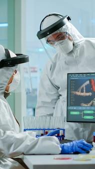 設備の整った実験室でウイルスの発生を調べているpcの前で議論している保護訴訟の科学者チーム治療を研究するためのハイテクを使用してワクチンの進化を分析している科学者のチーム