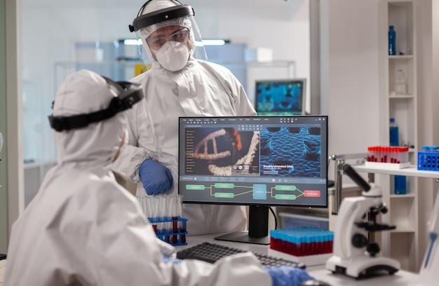 바이러스 개발을보고있는 pc 앞에서 치료를 논의하는 prorection 소송의 과학자 팀