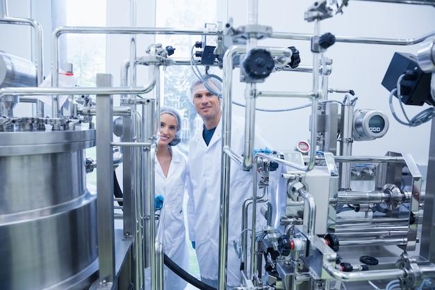 Scientist team behind metal gauge looking at camera in the factory