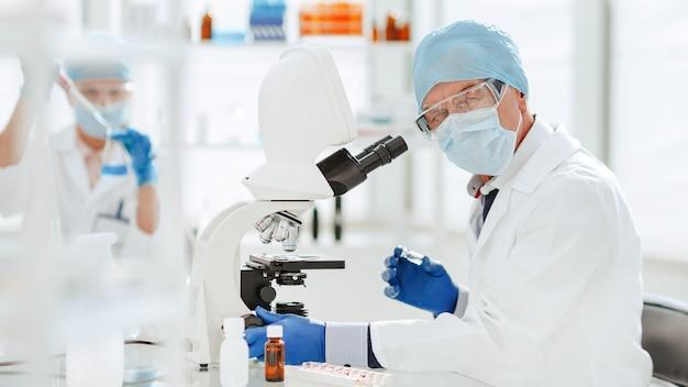 Ученый с помощью микроскопа в биохимической лаборатории