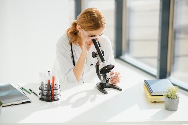 実験室で顕微鏡を使用している科学者、コロナウイルスcovid19ワクチンのテスト