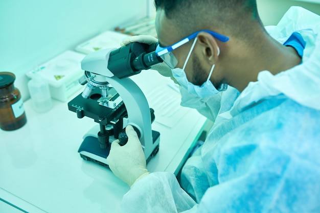 Scientist using microscope in medical lab