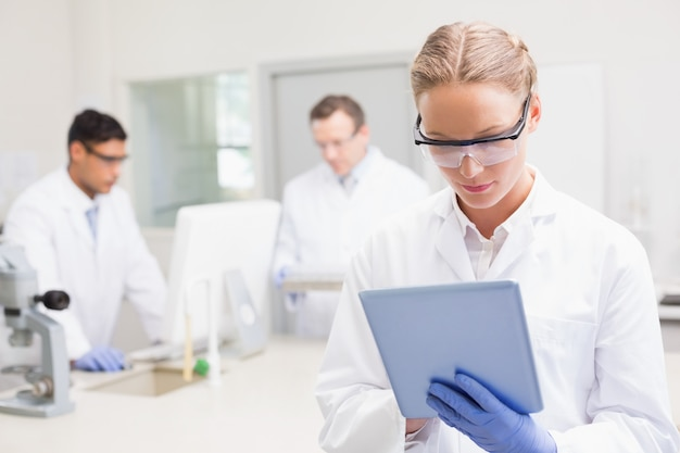 Scientist using tablet while colleagues working behind