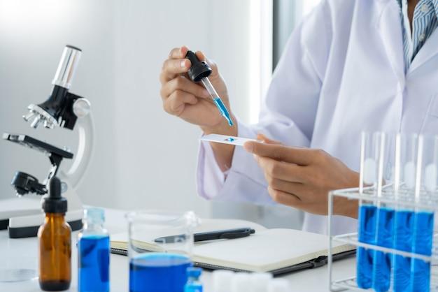과학자 착용 실험실 코트와 보호복은 실험, 실험실 및 개발 개념에서 시험관으로 연구를 하거나 조사를 하고 있습니다.