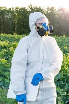 白い保護具、化学マスク、眼鏡をかけている科学者は、畑でノートパソコンを使用しています
