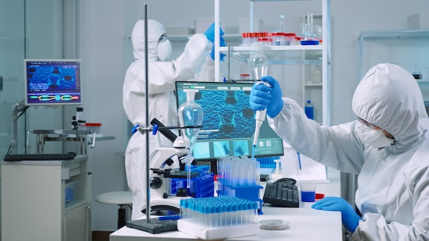 Scientist wearing coverall in equipped medical laboratory examining drug discovery with micropipette. biochemists analysing virus evolution using high tech researching vaccine against covid19