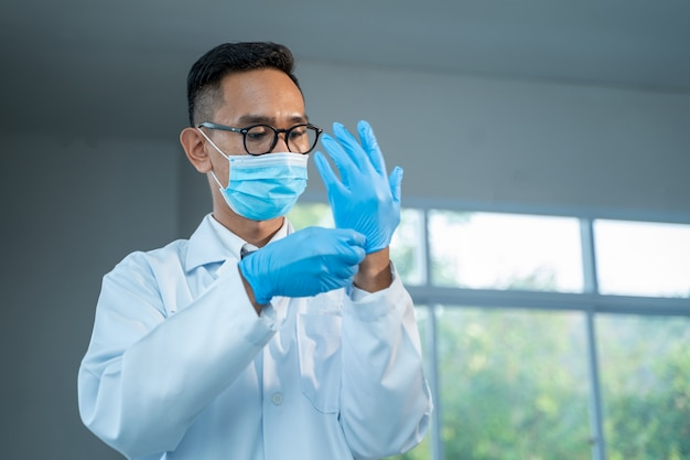 Scientist wearing glove.,doctors are wear medical rubber gloves for protection coronavirus disease 2019 (covid-19) ,coronavirus has turned into a global emergency.
