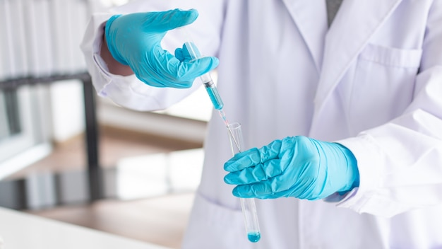 Scientist wearing lab coat and gloves taking a sample in syringe while working over scientific experiment in laboratory