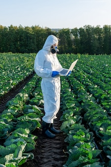 Scientist wearing in white protective suit chemical mask and glasses uses laptop on farm field