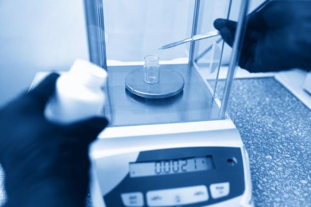 Ученый взвешивает химические вещества с помощью цифровых весов в граммах в химической лаборатории синего тонирования