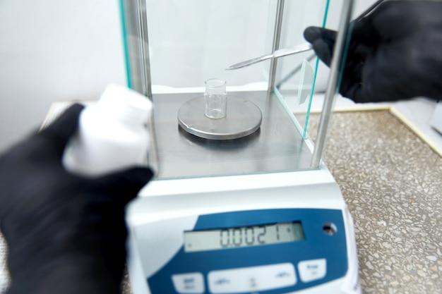 Ученый, взвешивающий химические вещества с помощью цифровых весов в граммах в химической лаборатории