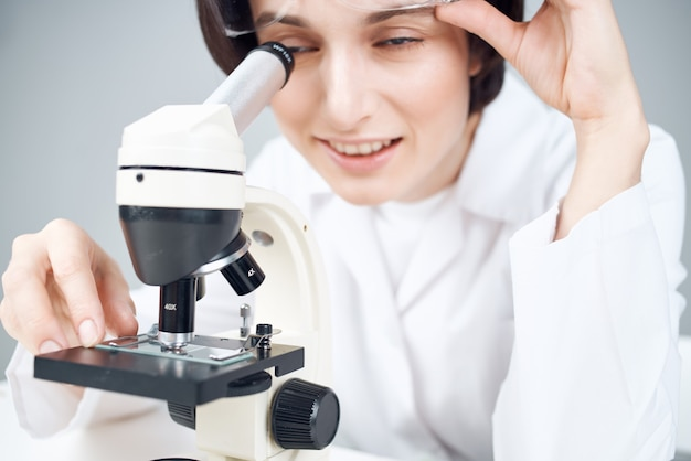 A scientist in a white coat looking through a microscope closeup laboratory