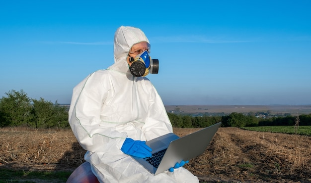 Scientist on white protective equipment chemical mask and glasses uses laptop on farm field