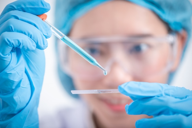 Scientist with equipment and science experiments ,laboratory glassware containing chemical liquid for design or decorate science or other your content and selective focus