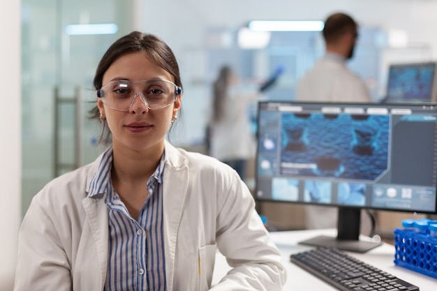 Scientist with lab coat sitting in laboratory looking at camera smiling