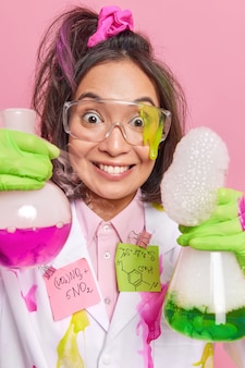 실험실 유리 제품을 가진 과학자는 다채로운 액체를 혼합하거나 재료가 화학 반응을 일으켜 실험실에서 연구를 수행합니다. 코트 보호 안경. 클리닉에서 긍정적인 건강 관리 연구원