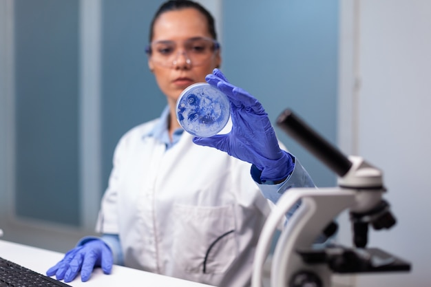Scientist woman analyzing petri dish with microorganism bacteria
