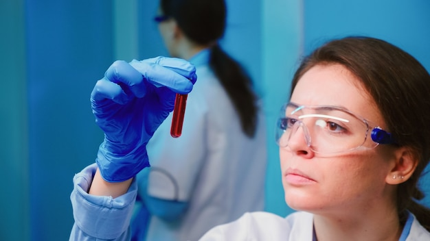 近代的な設備の整った実験室で働く血液サンプルと液体を調べる科学者の女性