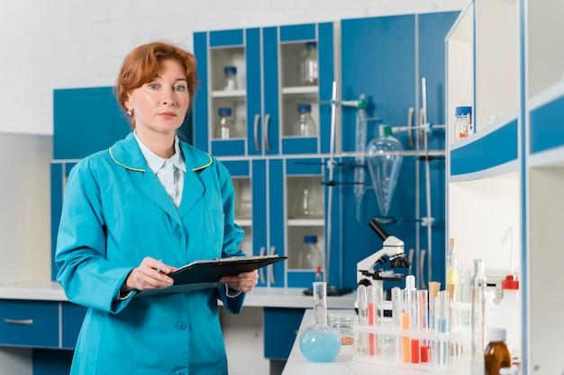 Donna dello scienziato che tiene una lavagna per appunti
