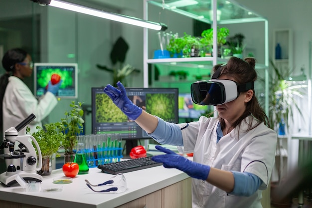 Scientist woman researcher wearing virtual reality headset developing new biotechnology for biological experiment. medical team working in microbiology laboratory analyzing dna test.
