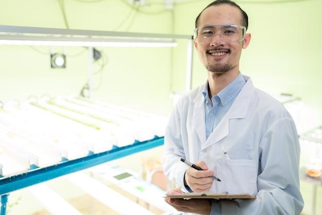 Ученый, занимающийся исследованиями в области сельскохозяйственных зеленых растений в теплице лаборатории биологических наук, органический экспериментальный тест для медицинской пищевой биотехнологии, биолог-эколог-ботаник в области выращивания сельскохозяйственных культур